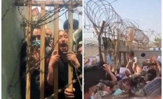 Mothers throw babies over airport's barbed wire begging soldiers to take them