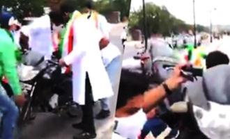 Viral: Congress workers throw bike into Hussain Sagar